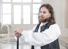Handsome man in medieval clothes with cane Stock Images