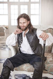 Handsome man in medieval clothes sitting in the chair Royalty Free Stock Image