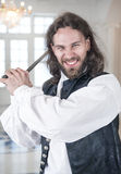 Handsome man in medieval clothes threaten with sword. Young handsome man in medieval clothes threaten with sword royalty free stock photography