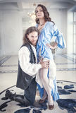 Handsome man in medieval costume seduces beautiful woman. Handsome men in medieval costume seduces beautiful women with long hair Stock Image