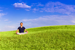 Handsome man meditating on the field. Stock Image