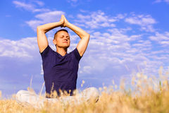 Handsome man meditating on the field. royalty free stock photo