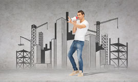 Handsome man with megaphone over concrete wall Stock Photo