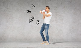 Handsome man with megaphone over concrete wall. Communication concept - handsome man with megaphone over concrete wall Stock Image