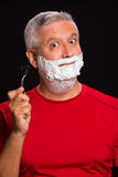Handsome man. Handsome middle age man with shave cream on a black background Royalty Free Stock Photo
