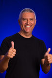 Handsome man. Handsome middle age man in a studio portrait with thumbs up sign Stock Image