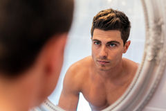 Handsome man in mirror. Handsome man looking in mirror after shaving Royalty Free Stock Images
