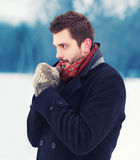 Handsome man in mittens freezes outdoors in winter Stock Photo