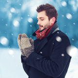 Handsome man in mittens freezes outdoors in winter day Stock Photos