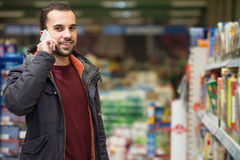Handsome Man On Mobile Phone At Supermarket Royalty Free Stock Images