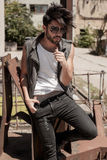 Handsome man model dressed punk, hipster posing dramatic in grun Stock Photography