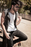 Handsome man model dressed punk, hipster posing dramatic in grun Royalty Free Stock Photos