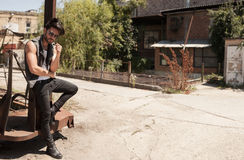 Handsome man model dressed punk, hipster posing dramatic in grun Stock Image