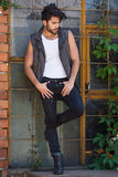 Handsome man model dressed punk, hipster posing dramatic in grun Royalty Free Stock Photo