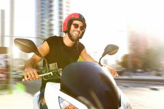 Handsome man on motorcycle ride in city smiling Stock Images