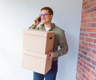 Handsome man with moving boxes calling by phone Royalty Free Stock Images