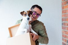 Handsome man with moving boxes and dog on white background Royalty Free Stock Image
