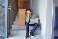 Handsome man with moving boxes and laptop sitting on stairs Stock Photo