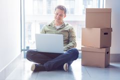Handsome man with moving boxes and laptop sitting on stairs Stock Images