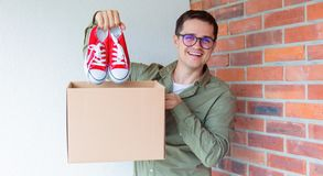 Handsome man with moving boxes and red gumshoes Stock Images
