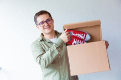 Handsome man with moving boxes and red gumshoes Royalty Free Stock Images