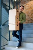 Handsome man with moving boxes sitting on stairs Stock Photo
