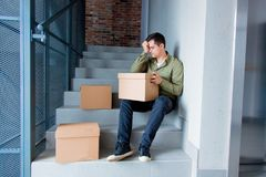 Handsome man with moving boxes sitting on stairs Royalty Free Stock Image