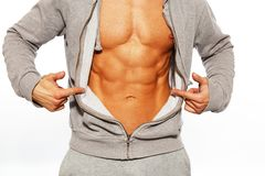 Handsome man with muscular body. Handsome man in grey hoodie showing his abdominal muscles Royalty Free Stock Photo