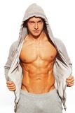 Handsome man with muscular body. Handsome man in grey hoodie showing his abdominal muscles Royalty Free Stock Photos