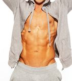 Handsome man with muscular body. Handsome man in grey hoodie showing his abdominal muscles Stock Photo