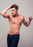 Handsome man with muscular body. Posing over gray background Stock Photography