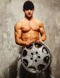 Handsome man with muscular body. Handsome sporty man with muscular body holding alloy wheel Stock Photo