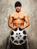 Handsome man with muscular body. Handsome sporty man with muscular body holding alloy wheel Royalty Free Stock Images