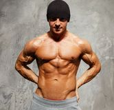 Handsome man with muscular body. Handsome man with muscular torso in beanie hat posing Stock Photography