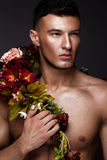 A handsome man with a naked torso, bronze tan and flowers on his body. Photo taken in studio Stock Image