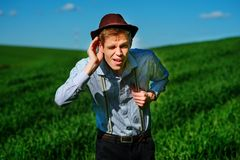 Handsome man in the nature tries to hear something with putting his hand to his ears royalty free stock images