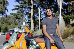 Handsome man near scooter Stock Images
