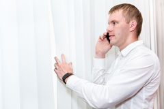 Handsome man near window blinds with phone Royalty Free Stock Photography