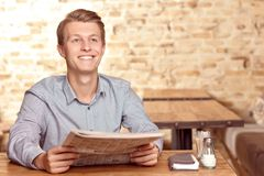 Handsome man with newspaper in cafe Stock Photos
