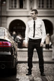 Handsome man next to the car in the city Stock Images