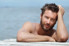 Handsome Man with No Shirt at the Sea. Close up Portrait of Smiling Gorgeous Handsome Man with No Shirt Posing at the Sea Royalty Free Stock Photos