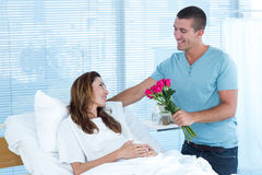 Handsome man offering bouquet of flowers to his pregnant wife Royalty Free Stock Images