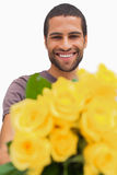 Handsome man offering bunch of yellow roses. On white background Royalty Free Stock Photography