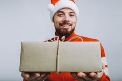 Handsome man offering a christmas gift. Isolated on white background. Handsome man offering a christmas gift. Smiling guy is proposing big present for you at Royalty Free Stock Image