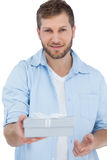 Handsome man offering a present looking at camera Stock Photography