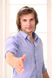 Handsome man offering to shake his hand Royalty Free Stock Images
