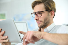 Handsome man at office using tablet Royalty Free Stock Photos
