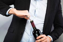 Handsome man opening bottle of wine Royalty Free Stock Images
