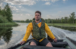 Handsome man is operating of boat on the river Royalty Free Stock Photos