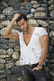 Handsome man outdoor in front of stone wall Stock Photos